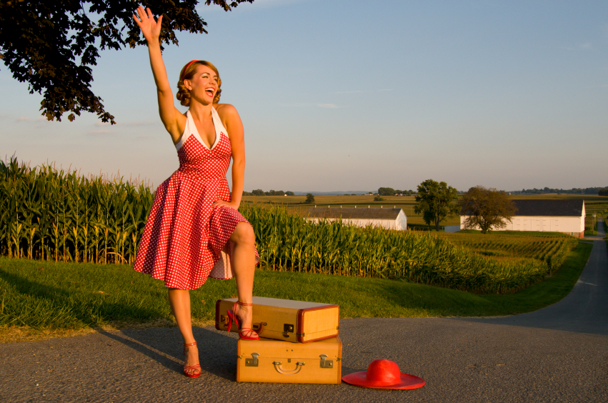 young woman dressed up in red vintage attire waiving for her ride in the Pennsylvania country side
