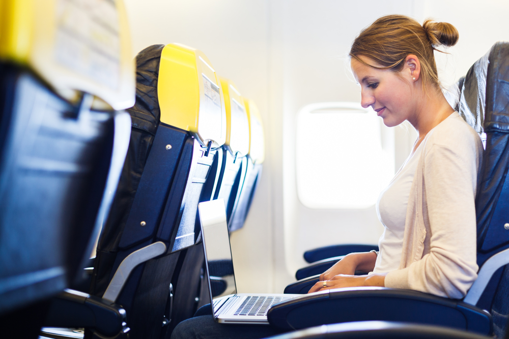 Woman working on her laptop in an airplane.