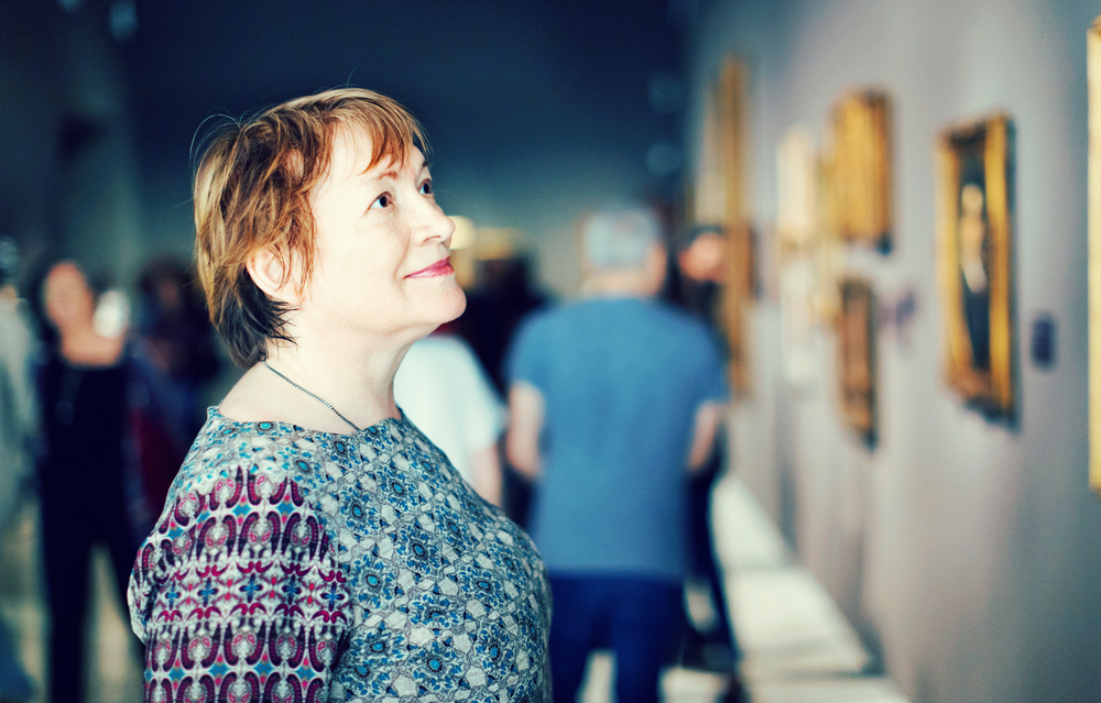 Woman examining picture at exhibition
