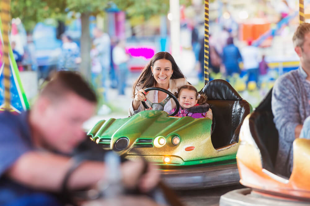 Mother and daughter enjoying a bumper car ride at amusement park